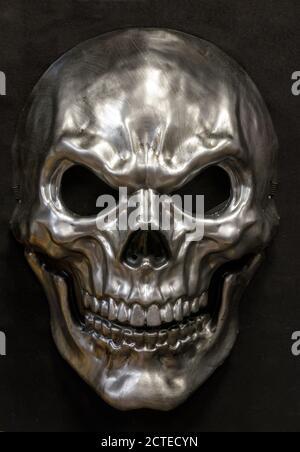 Masque métallique de crâne sinistre isolé contre un arrière-plan noir