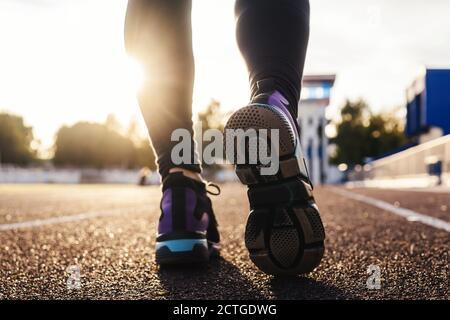 Les pieds de course sur les pistes du stade, à proximité de la chaussure. Femme fitness coucher de soleil jogging entraînement welness concept.