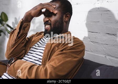 Attention sélective à l'homme afro-américain qui a mal de tête Banque D'Images
