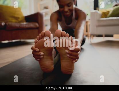 Gros plan d'une jeune femme en bonne santé qui touche les pieds tout en étirant exercice à la maison