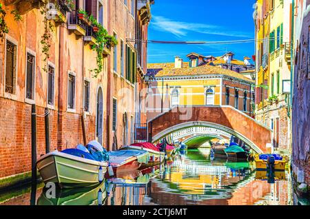 Paysage urbain de Venise avec gondoles et bateaux à moteur amarrés sur le canal étroit d'eau à proximité de bâtiments colorés et pont en pierre, région de Vénétie, nord de l'Italie, ciel bleu en été, vue typiquement vénitienne