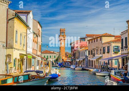 Îles de Murano avec tour d'horloge Torre dell'Orologio, bateaux et bateaux à moteur dans le canal d'eau, bâtiments traditionnels colorés, lagune vénitienne, région de Vénétie, Italie du Nord. Carte postale de Murano.