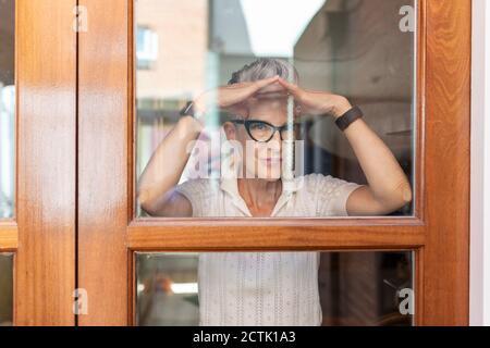 Femme âgée faisant un geste de la main tout en regardant par la fenêtre à la maison
