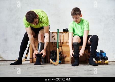Père et fils portant des chaussettes assis sur une caisse en bois au tribunal
