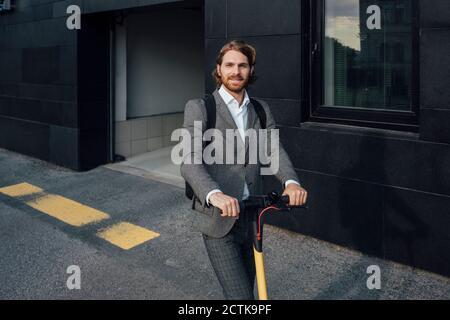 Homme d'affaires plein de confiance, volant d'un scooter électrique pour se déplacer dans les transports en commun dans le centre-ville