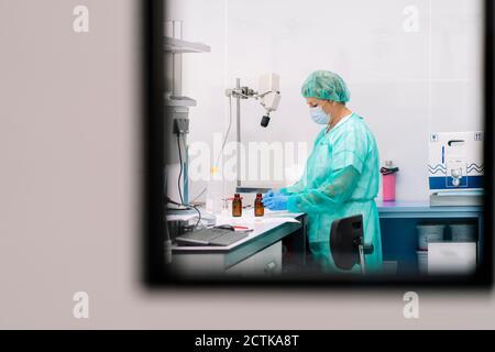Femme scientifique travaillant à la table en laboratoire, vue à travers la fenêtre