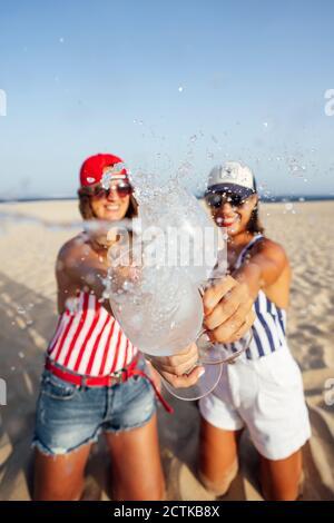 Des amies ludiques barbotent en buvant un verre tout en dorant à la plage jour ensoleillé Banque D'Images