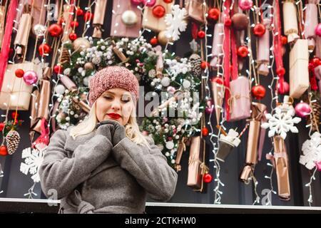 Un portrait d'une jeune belle femme prie à la rue de noël, Noël. Banque D'Images