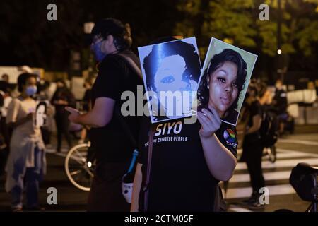 Washington, DC, Etats-Unis, 23 septembre 2020. En photo : un manifestant à la Marche pour la Justice pour Breonna Taylor affiche deux photos de Breonna Taylor, qui ont été transportées par de nombreux manifestants ce soir, sur Black Lives Matter Plaza. La Marche pour la justice de Breonna Taylor a été un événement national qui a eu lieu dans de nombreuses villes à travers les États-Unis. La marche a été en réponse à l'annonce plus tôt dans la journée que la police qui a tué Breonna Taylor pendant qu'elle dormait ne serait pas accusée de sa mort. Crédit : Allison C Bailey/Alamy