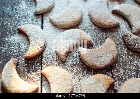 Sablés nouvel an, biscuits de Noël en forme de lune. Un enfant saupoudrer les biscuits avec du sucre en poudre. Bébé et biscuits. Les mains de l'enfant