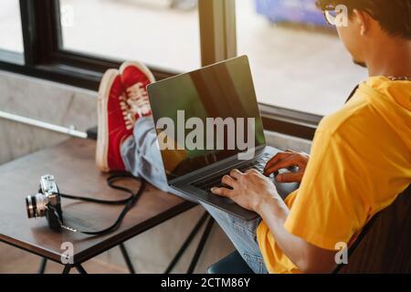 Gros plan asiatique freelance homme réécrivant du contenu dans les réseaux sociaux via ordinateur portable tout en se reposant dans un café moderne, idées de travail en ligne Banque D'Images