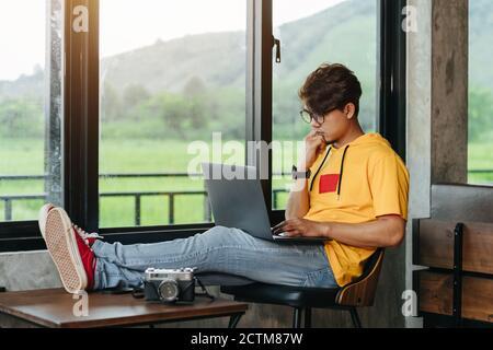 Homme indépendant asiatique assis et pensant du contenu dans le réseau social via ordinateur portable tout en se reposant dans un café moderne, idées de travail en ligne Banque D'Images