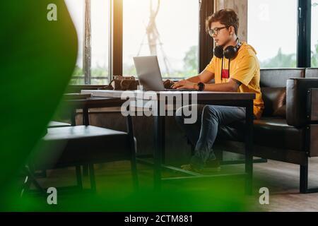 Homme indépendant asiatique réécrivant du contenu dans un réseau social via un ordinateur portable tout en se reposant dans un café moderne, idées de travail en ligne Banque D'Images