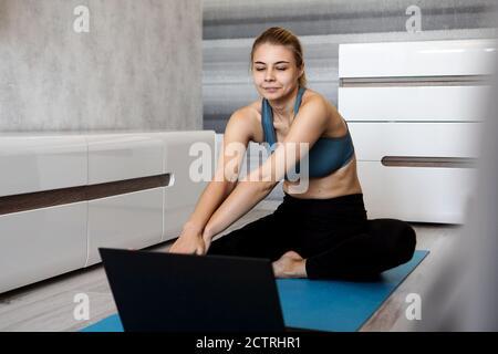 Jolie jeune femme dans les vêtements de sport regardant la vidéo en ligne sur ordinateur portable et faisant des exercices à la maison. Formation à distance avec entraîneur personnel, formation en ligne