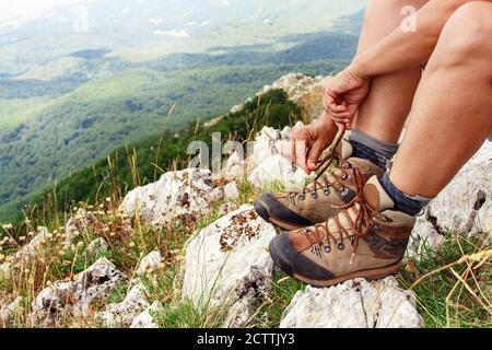 Femme de randonnée nouant des lacets de bottes de trekking gros plan panorama