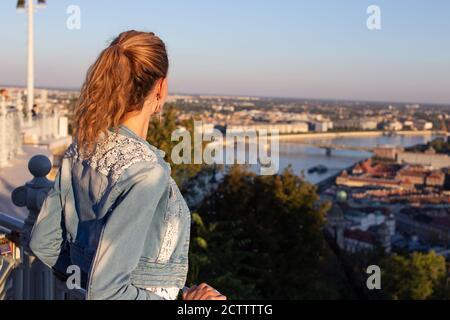 Femme urbaine se demandant dans le panorama de la ville au coucher du soleil Banque D'Images