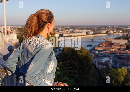 Jeune femme urbaine se demandant dans la ville panorama coucher de soleil Banque D'Images