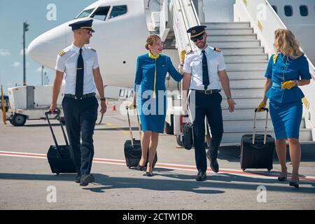 Une équipe amicale et heureuse de pilotes et d'hôtesses portant un uniforme va à l'aéroport avec des sacs à roulettes