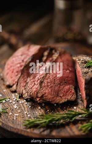 Bœuf moyen juteux entrecôtes de bœuf en tranches de bœuf sur une planche de bois avec épices et sel. Steak prêt à manger avec des ingrédients sur une planche à découper.
