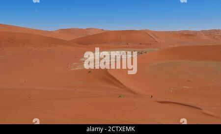 Vue aérienne de grandes dunes de sable orange avec deux personnes marchant dans la vallée à Sossusvlei, désert du Namib, Namibie, Afrique. Ciel bleu sans nuages.
