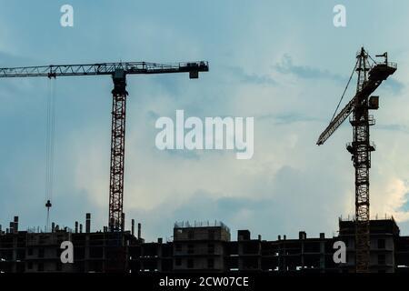 Grues à tour au-dessus du bâtiment en construction.