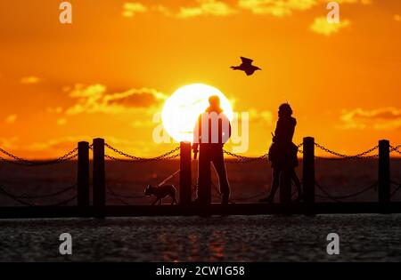 Les gens sont vus au lac Marine pendant que le soleil se couche sur le canal de Bristol, Weston-super-Mare, Grande-Bretagne, 26 septembre 2020. REUTERS/Peter Cziborra