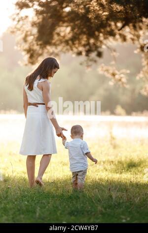 mère et fils marchant dans le parc le jour ensoleillé de l'été. fête des mères, journée du bébé. concept de famille Banque D'Images