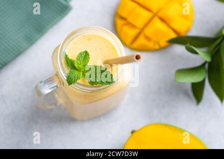 Smoothie mangue dans un pot en verre avec paille de bambou écologique décoration avec feuilles de menthe sur fond de béton gris