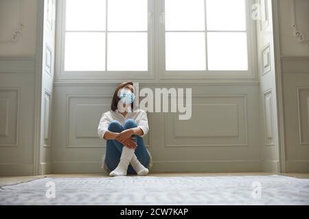 jeune femme asiatique en quarantaine à la maison portant un masque facial assis sur les jambes de plancher croisées, en regardant triste et déprimé Banque D'Images