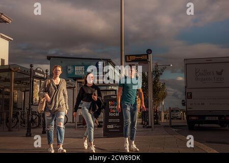 La vie quotidienne. Les filles et l'homme marchant vers l'appareil photo dans la rue principale autour de la gare. Greystones. Irlande.