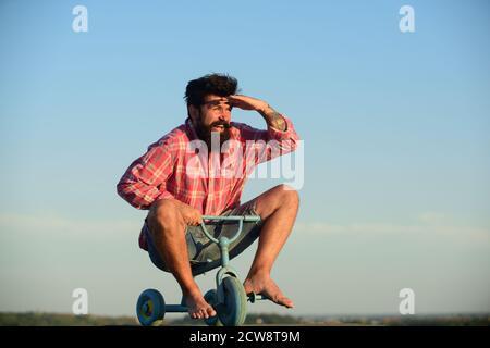 Un fou qui fait du vélo. Drôle d'homme sur un vélo pour enfants.