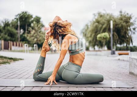 Jeune femme sportive avec de longs cheveux en surpiste grise faisant des exercices d'étirement dans la rue. Mode de vie actif, concept de yoga.