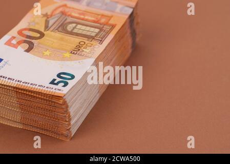 Un énorme tas de 50 billets en euros sur fond marron clair. Espace de copie disponible pour communiquer votre propre message.
