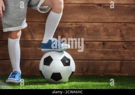 Un petit enfant mignon rêve de devenir joueur de football. L'enfant joue au football.
