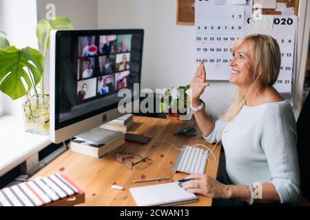 Femme mûre souriante ayant des appels vidéo via l'ordinateur le bureau à domicile. Vidéoconférence en ligne pour les réunions d'équipe depuis la maison. Femme d'affaires attirante