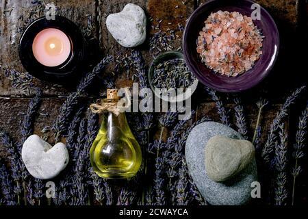 Concept SPA. Plat de fleurs de lavande fraîches et sèches, huile essentielle, sel rose, pierres en forme de coeur, bougie aromatique sur carreaux de céramique brun foncé Banque D'Images