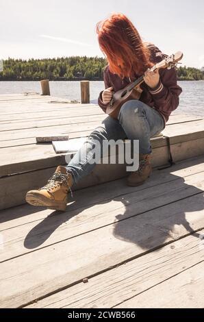 Une jeune fille aux cheveux rouges chante une chanson avec ukulele assis sur une jetée en bois par beau temps