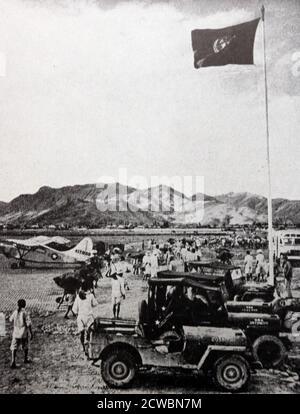 Photographie en noir et blanc de la guerre de Corée (1950-1953); un drapeau aux couleurs de l'ONU survole un aérodrome.
