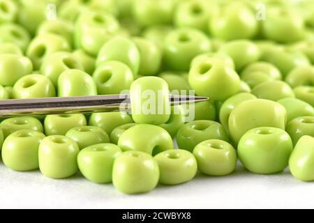 Les perles se répandent sur fond blanc avec l'aiguille. Perles avec aiguille . Gros plan, macro, il est utilisé dans la finition des vêtements de mode. Faire collier de perles, perles f