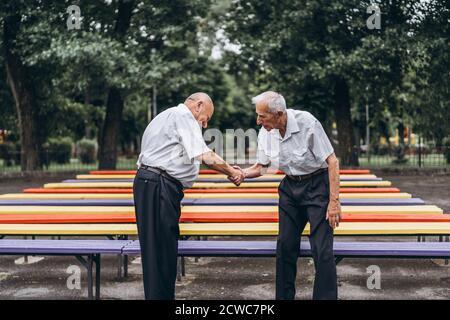 Deux vieux hommes adultes âgés ont une conversation à l'extérieur dans le parc de la ville Banque D'Images