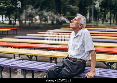 Les hommes adultes âgés fument de la cigarette à l'extérieur dans le parc de la ville assis sur la banquette