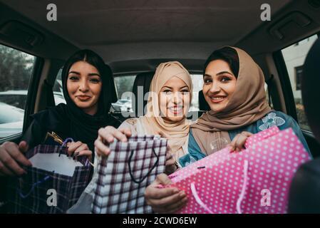 Trois femmes amies qui sortent à Dubaï. Les filles portant l'abaya traditionnelle des émirats arabes unis Banque D'Images