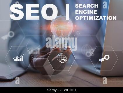 Homme d'affaires tenant une ampoule assise au bureau, Seo Collage avec texte