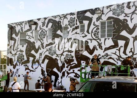 Street artist Shepard Fairey (lower left in gray shirt) puts the finishing touches on the mural titled 'Power and Glory' in the Wynwood section of Miami December 3, 2014, during a satellite event to the annual Art Basel Miami Beach extravaganza. As well as attracting major international galleries and wealthy art buyers, the Art Basel week draws some of the world's top street artists to South Florida. Miami is readying for the 13th installment of Art Basel Miami Beach, among the world's most important contemporary art fairs, a five-day event that has become a magnet for high-end real estate and