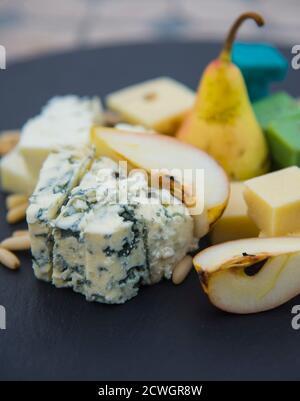 Morceaux de différents fromages, poires mûres et noix de pin. Produit laitier sur l'assiette noire