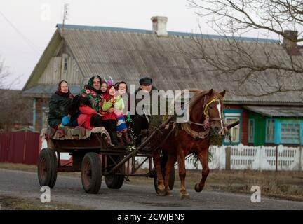Performers ride on a horse-drawn cart as they sing Christmas carols, locally known as 'Kolyadki', in the village of Gantsevichi, about 180 km (112 miles) southeast of Minsk, January 13, 2012. Many Orthodox Belarussians mark New Year according to the Julian calendar on January 13.  REUTERS/Vasily Fedosenko(BELARUS - Tags: SOCIETY ANIMALS)