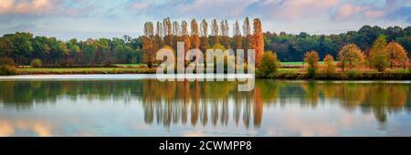 Arbres et nuages réflexions sur un étang en automne, paysage panoramique en Bourgogne, France
