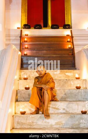 Portrait jeune débutant moine assis dans l'escalier à l'ancien temple et de nombreux fond de bougie, province d'Ayutthaya, Thaïlande