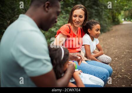 Une famille heureuse se reposant sur un sentier dans le parc