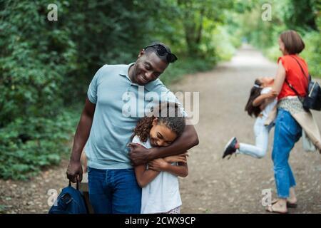 Père et fille heureux qui s'embrasse sur le sentier du parc